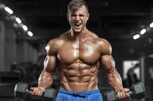 Man with muscles lifting dumbbells