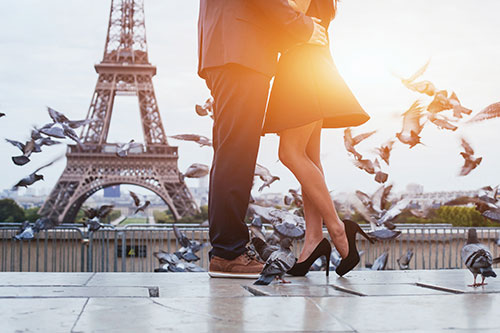 Man and Woman holding each other in front of Tour D'Eiffel in Paris, France