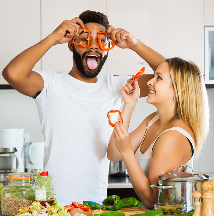 Couple cooking together being goofy