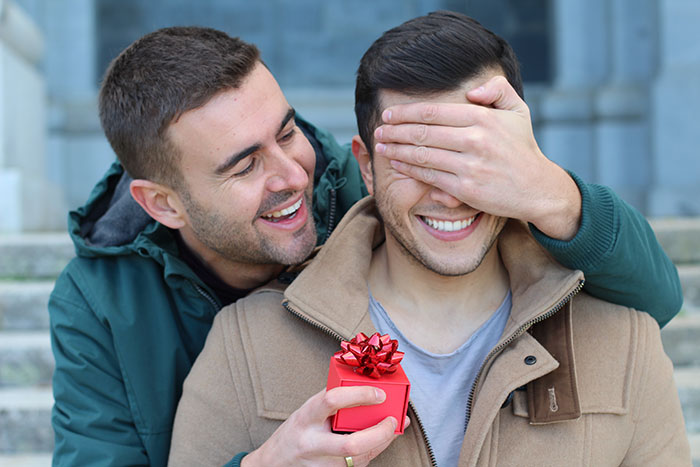 Couple gift giving, man behind other man holding hand over eyes with surprise gift