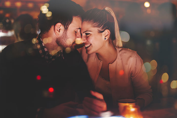 Couple Smiling at one another over drinks